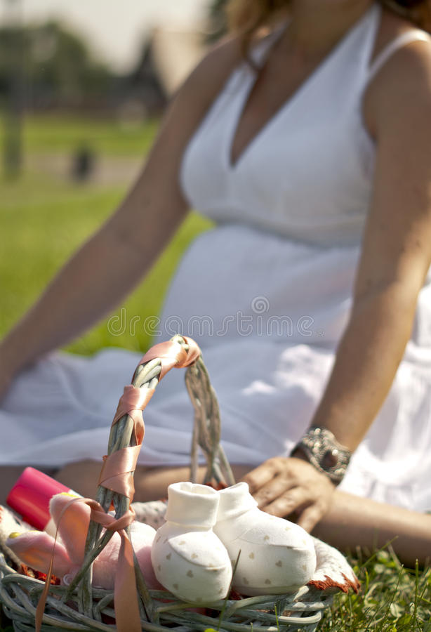 Pregnant woman is sitting on the grass. With a gift basket stock photo