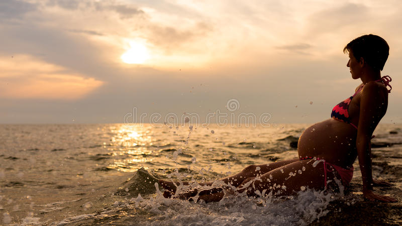 Pregnant woman sitting in the shallow water. Pregnant short-haired woman wearing a striped bathing suit while sitting in the shallow water of the sea, at sunset royalty free stock image