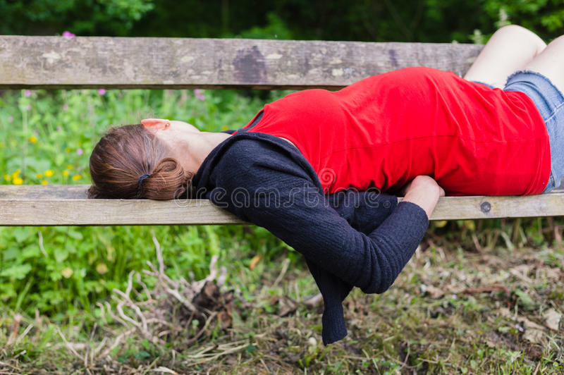 Pregnant woman sleeping on bench in forest. A young pregnant woman is sleeping on a bench in the forest royalty free stock photo
