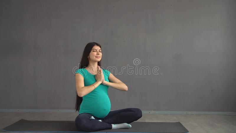 Pregnant woman in sportswear engaged in yoga. Active lifestyle of a pregnant girl. royalty free stock photos