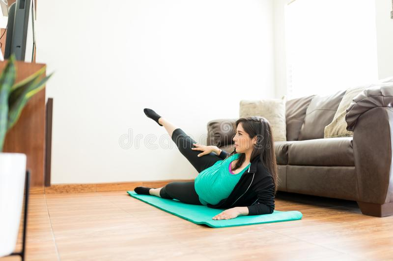 Pregnant Woman In Sportswear Exercising At Home royalty free stock photography