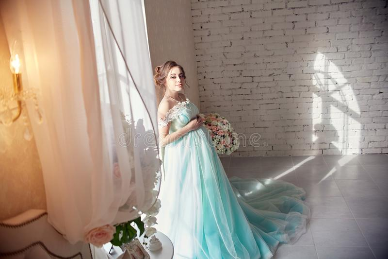 Pregnant woman standing at the window in the beautiful azure dress. Portrait of a girl preparing to become a mother. The woman in stock photos
