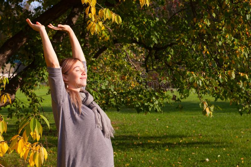 Pregnant woman stretching early in morning outdoor. Profile of young expectant female reaching for sun. Enjoy nature, peacefulness stock photo