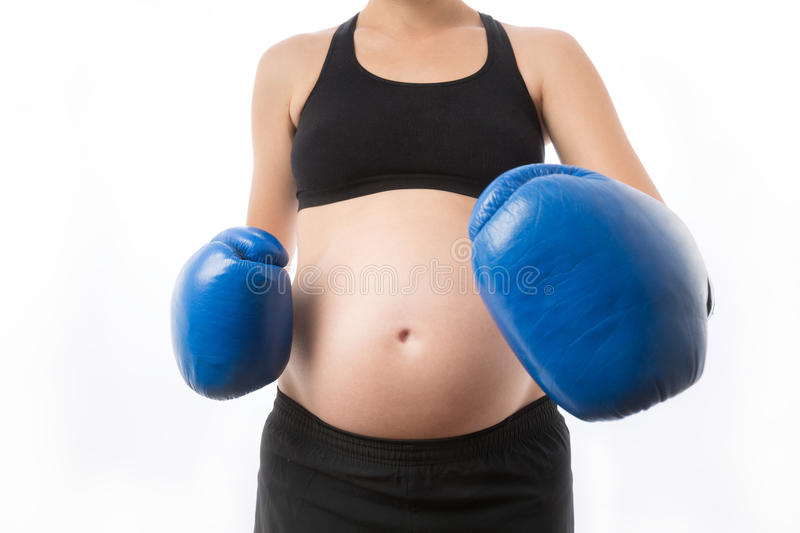 Pregnant woman strikes in boxing gloves royalty free stock photos