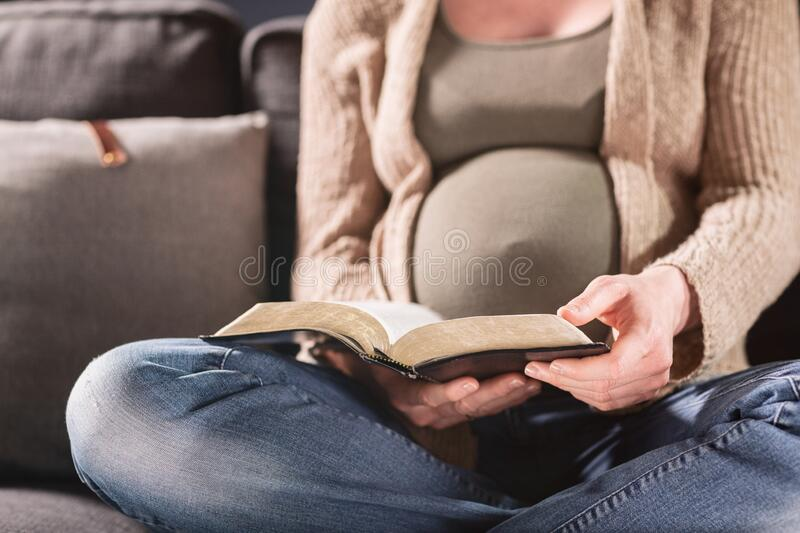 Pregnant Woman Studying the Bible at Home stock images