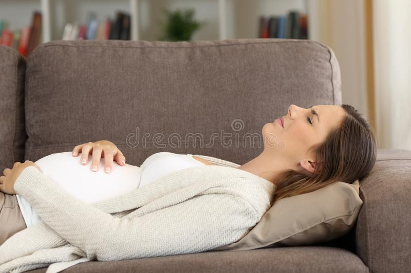Pregnant woman suffering belly ache at home. Pregnant woman suffering belly ache lying on a sofa at home stock photos