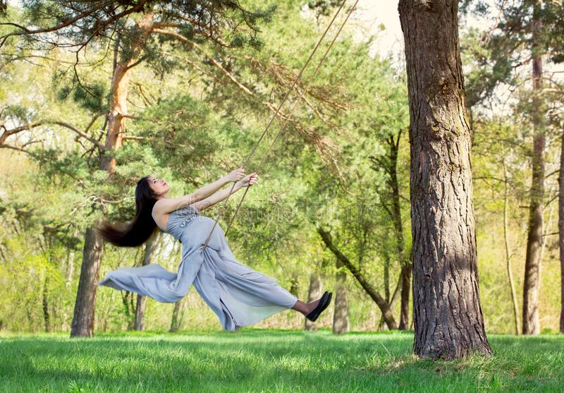 Pregnant woman swinging on a swing royalty free stock photography