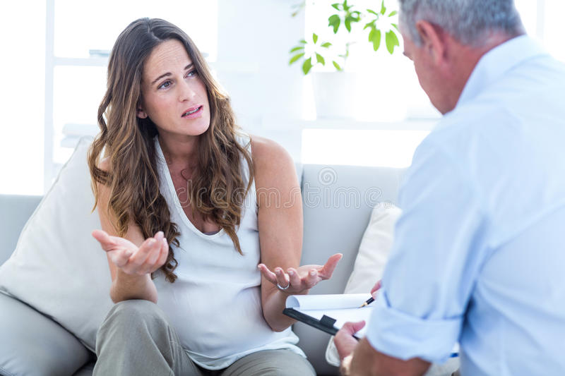 Pregnant woman talking with psychiatrist. Depressed pregnant women talking with psychiatrist in clinic stock photo