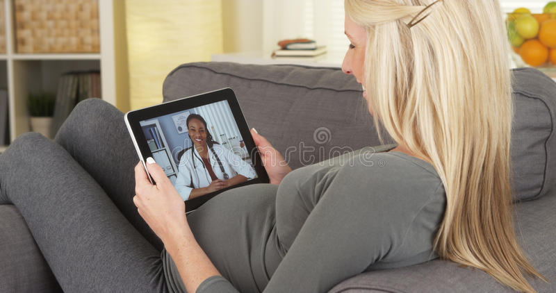 Pregnant woman talking to doctor on tablet. Pregnant women talking to doctor on tablet at home stock images