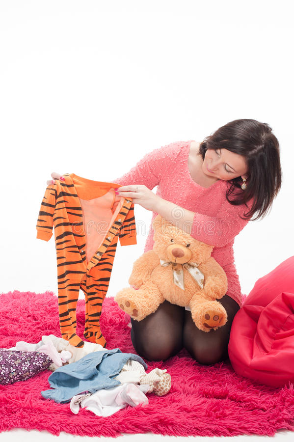 Pregnant Woman With Teddy Bear And Children S Clothes Stock Photography