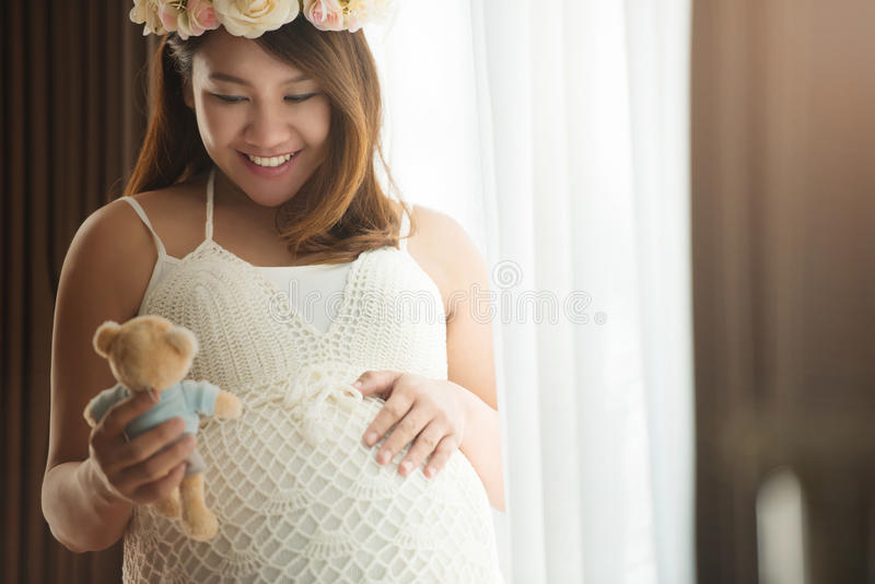 Pregnant woman and teddy bear doll. Pregnant woman holding a teddy bear doll at home stock images
