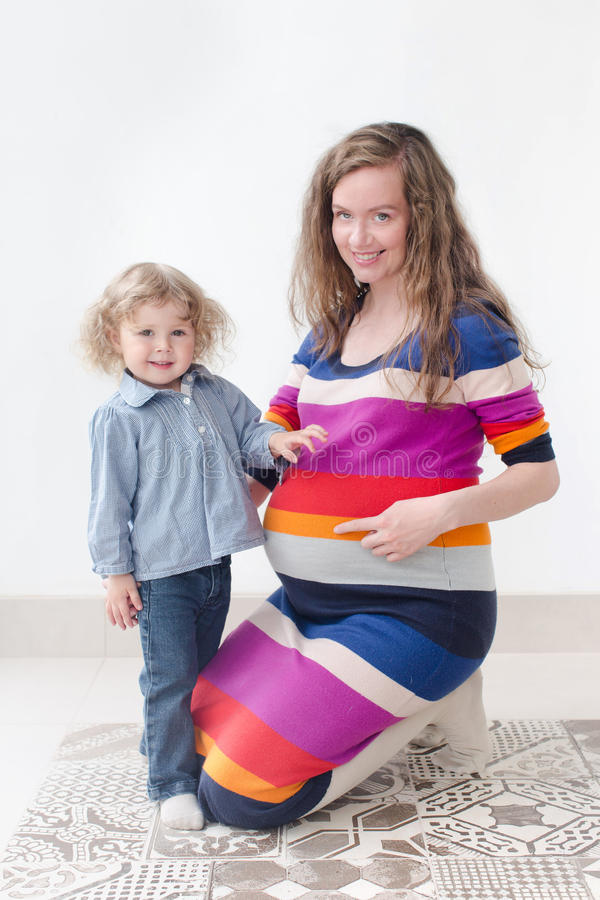 Pregnant woman together with child studio portrait royalty free stock photography