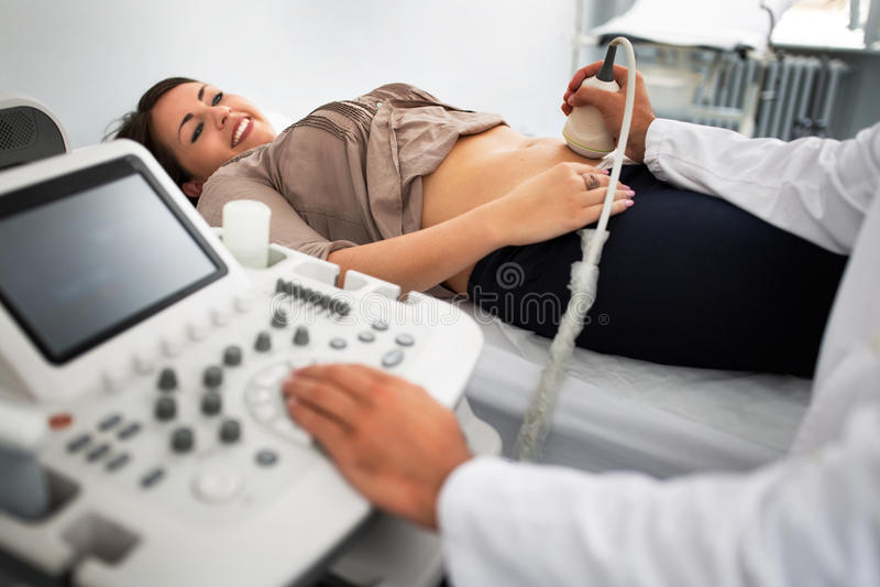 Pregnant woman undergoing ultrasound test. Pregnant women undergoing ultrasound test at gynecologist office stock photos