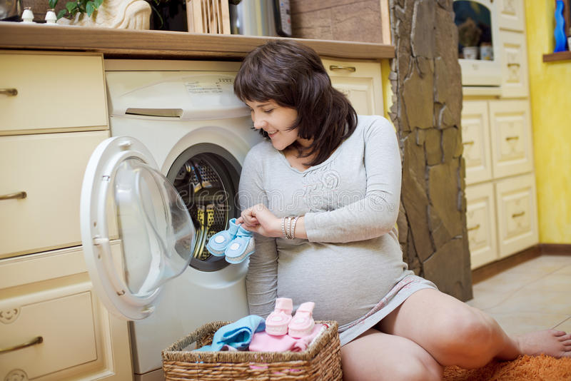 Pregnant woman washes baby clothes. Happy pregnant woman washes baby clothes royalty free stock photography