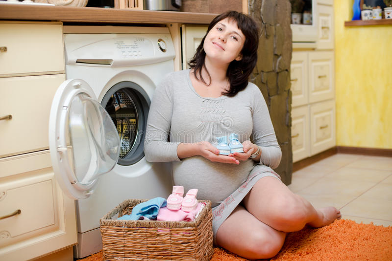 Pregnant woman washes baby clothes. Happy pregnant woman washes baby clothes stock image