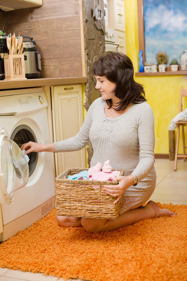 Pregnant woman washes baby clothes. Happy pregnant woman washes baby clothes stock images