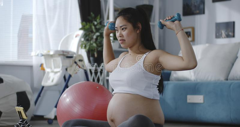 Pregnant woman watching tutorial video during workout royalty free stock photos