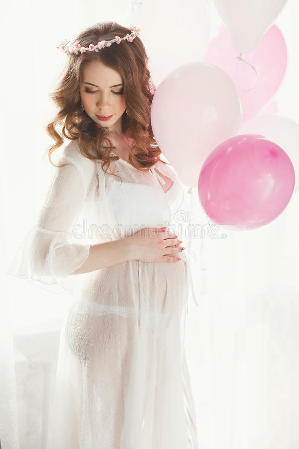 Pregnant woman in a white nightgown with balloons. royalty free stock image
