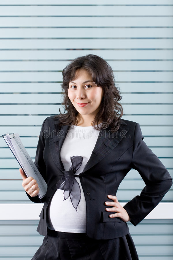 Pregnant woman at work stock images