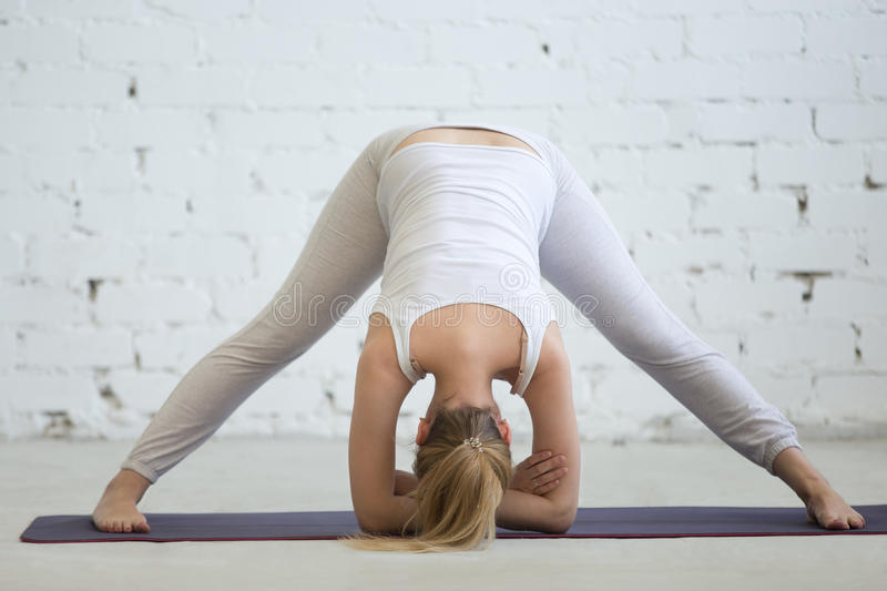 Pregnant woman working out, doing yoga pose royalty free stock image