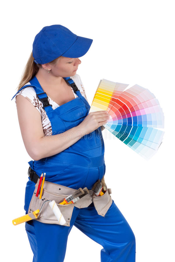 The pregnant woman in working overalls stock image
