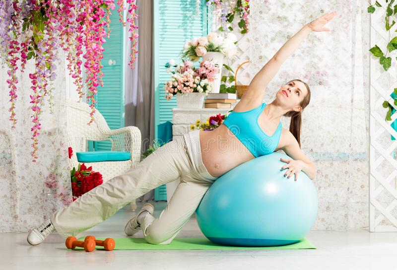 Pregnant woman during workout stock images