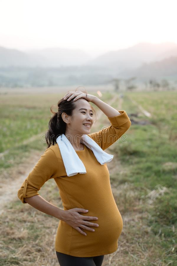 Pregnant woman workout outdoor. Active asian pregnant woman workout outdoor royalty free stock image