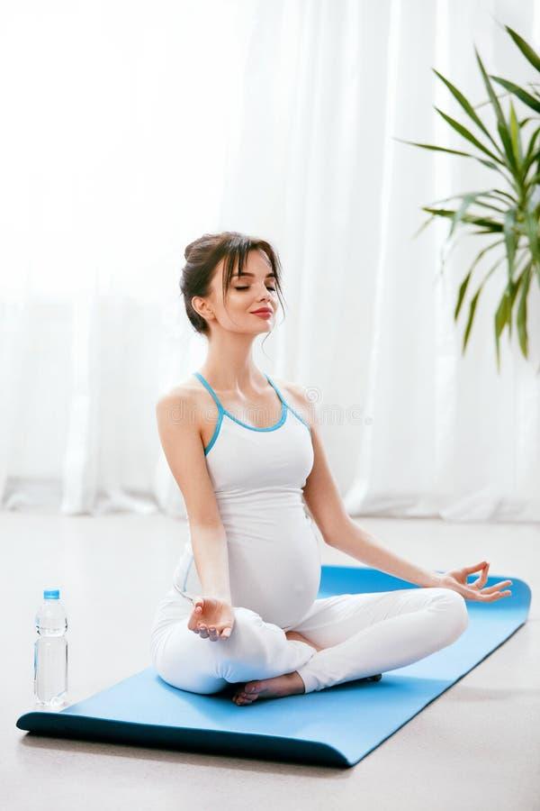 Pregnant Woman Yoga. Pregnant Girl Exercising At Home royalty free stock photo