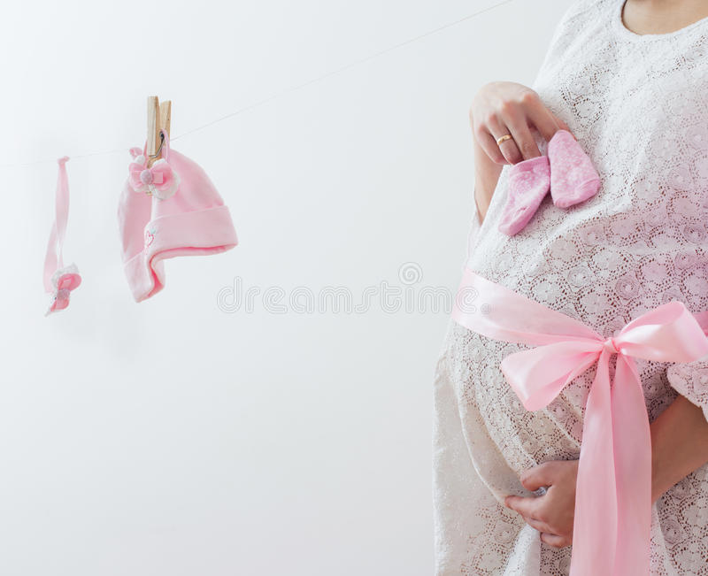 Pregnant women with baby clothes. Pregnant woman with pink baby clothes stock images