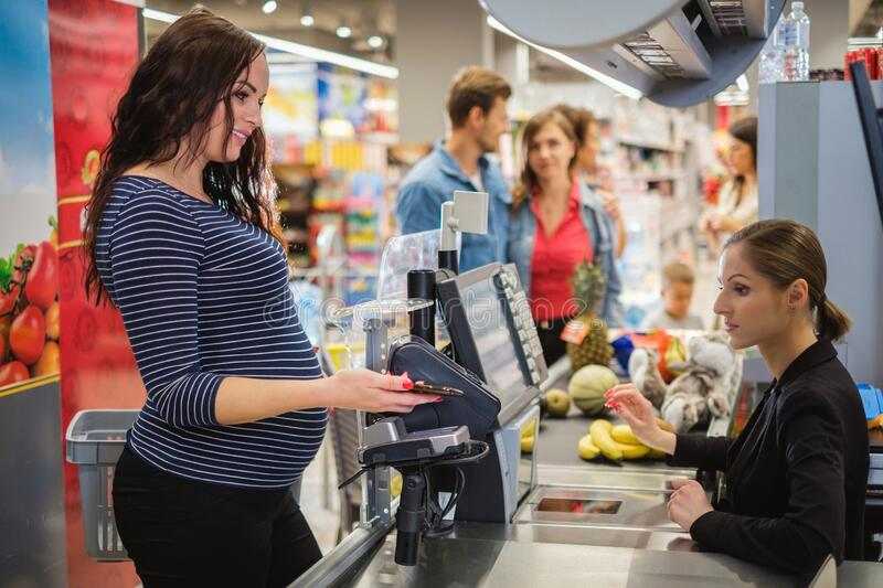 Pregnant woman buying goods in a grocery store royalty free stock photos