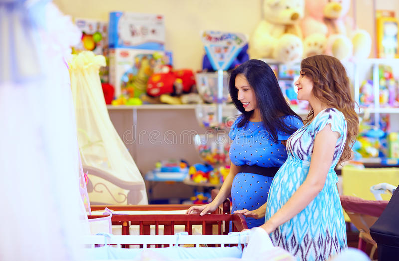 Pregnant women choosing cot for baby stock photos
