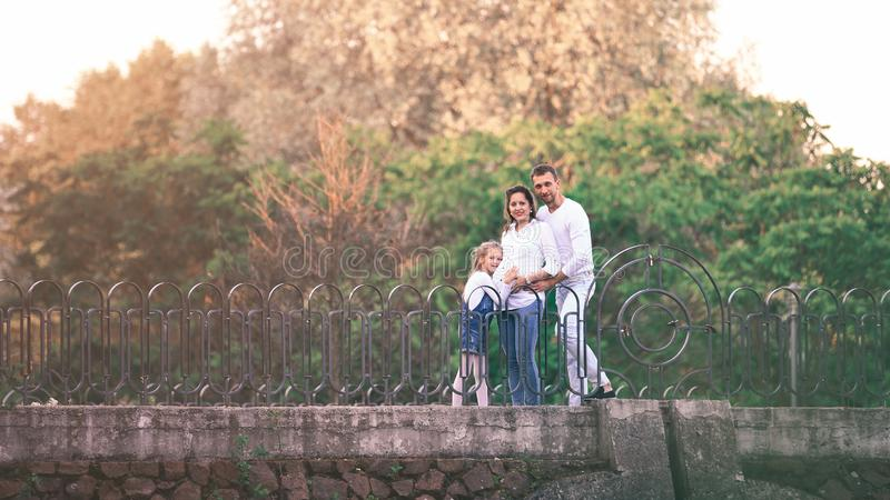 Pregnant woman with her daughter and husband in the park on the bridge royalty free stock image