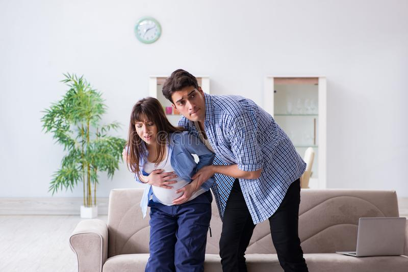 The pregnant woman with husband at home stock photo