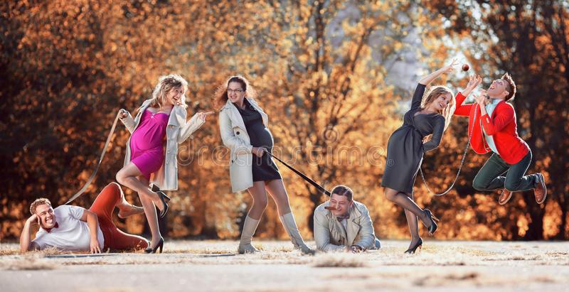 Pregnant women with husbands in the dog leash stock image