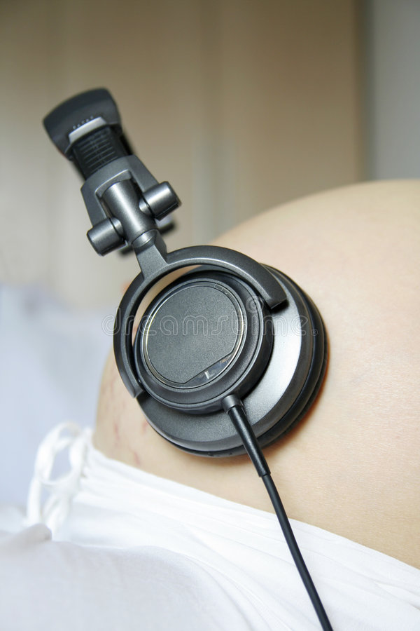 Pregnant women listen music stock photo