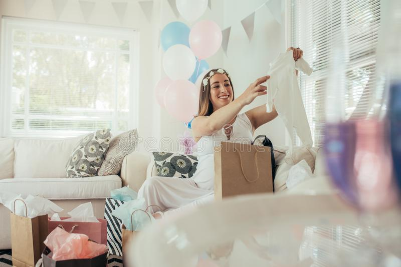 Pregnant woman opening a new gift after baby shower stock image