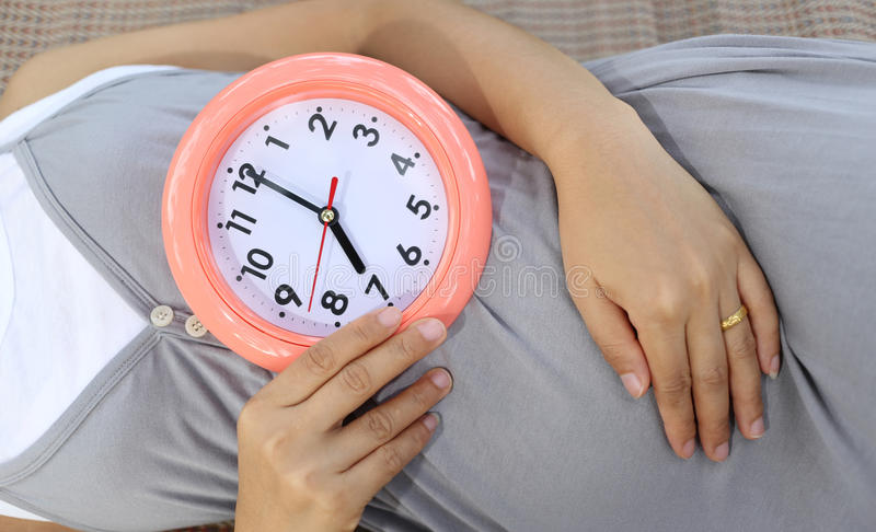 Pregnant women show clock on her belly to tell the time. stock photo