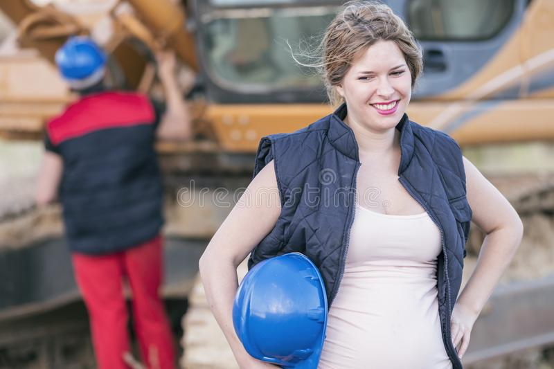 Pregnant worker woman portrait with man repairing bulldozer in b stock images