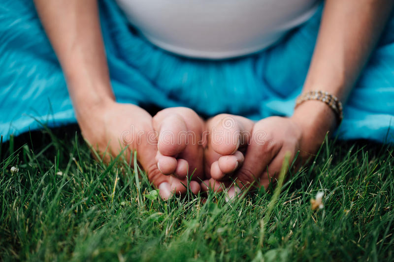 Pregnant yoga in the lotus position. in the park on the grass, doing exercises, stretching, outdoor, . feet close-up royalty free stock image