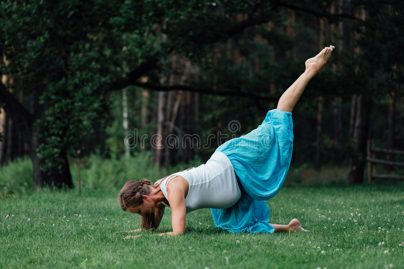 Pregnant yoga prenatal maternity doing different exercises. in the park on the grass, breathing, stretching, statics. Outdoor, forest. concept of healthy stock photo