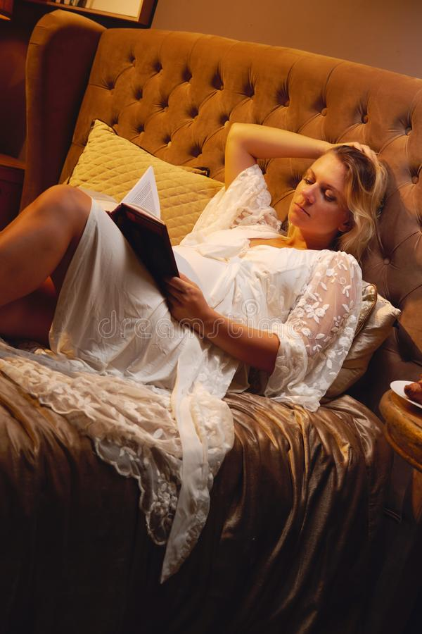 Pregnant young blond woman in rest gown lying on the bed at bedroom and reading a book about maternity or chicklit royalty free stock photo