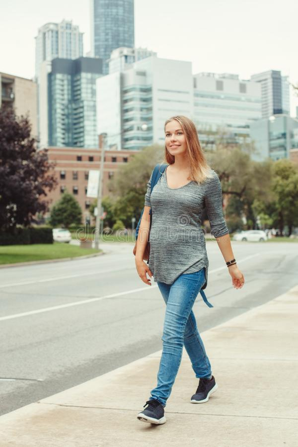 Pregnant young blonde Caucasian woman walking in busy urban city royalty free stock photography