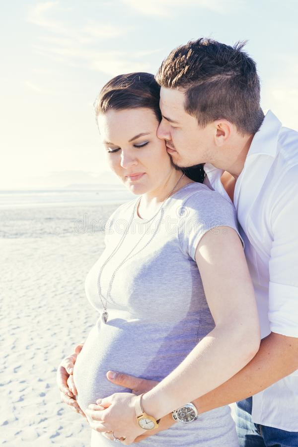 Pregnant young couple interacting, standing outdoors. Beach scene, embracing, with casual wear eyes closed royalty free stock photography