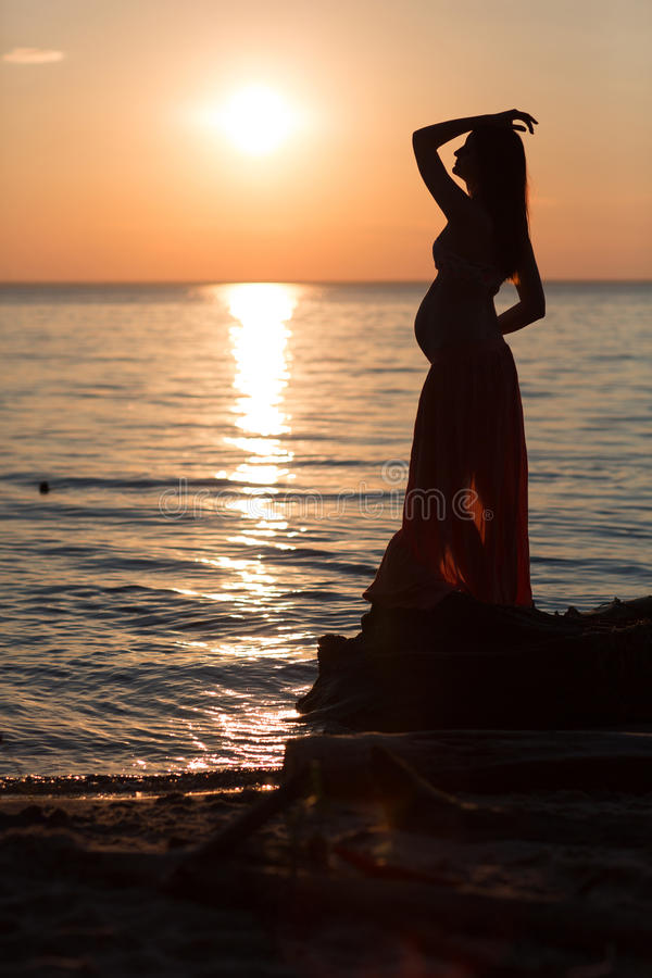 Pregnant young girl on the beach at sunset on the beach royalty free stock images