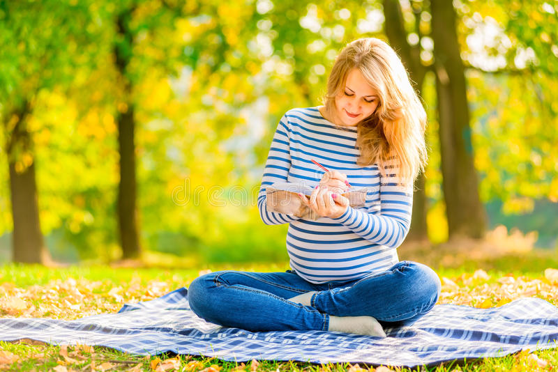 Pregnant young girl makes a shopping list royalty free stock image
