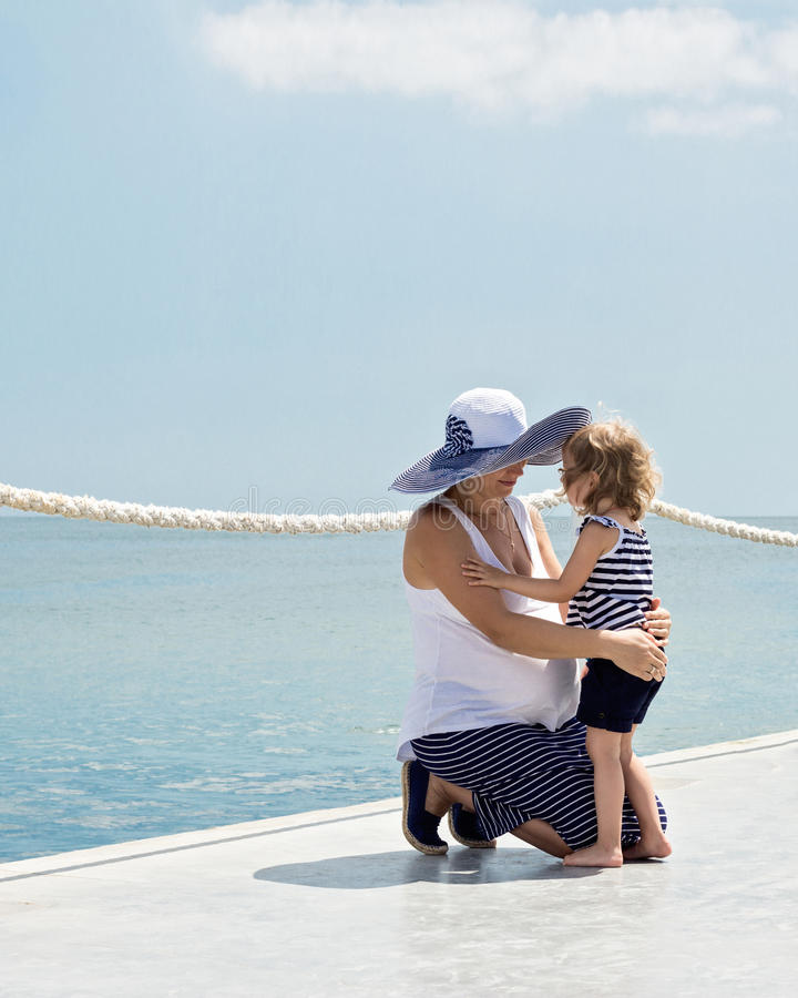 A pregnant young mother with a small daughter (3 years old) on t stock images