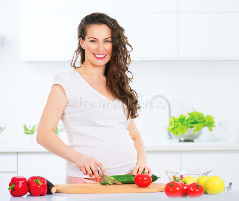 Pregnant young woman cooking vegetables. Healthy food stock photo