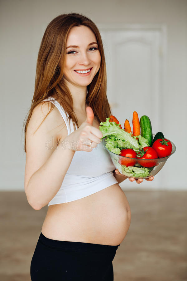 Pregnant Young Woman Cooking vegetables. Healthy Food - Vegetable Salad. Diet. Dieting Concept. Healthy Lifestyle. Cooking At Home. Prepare Food royalty free stock photo