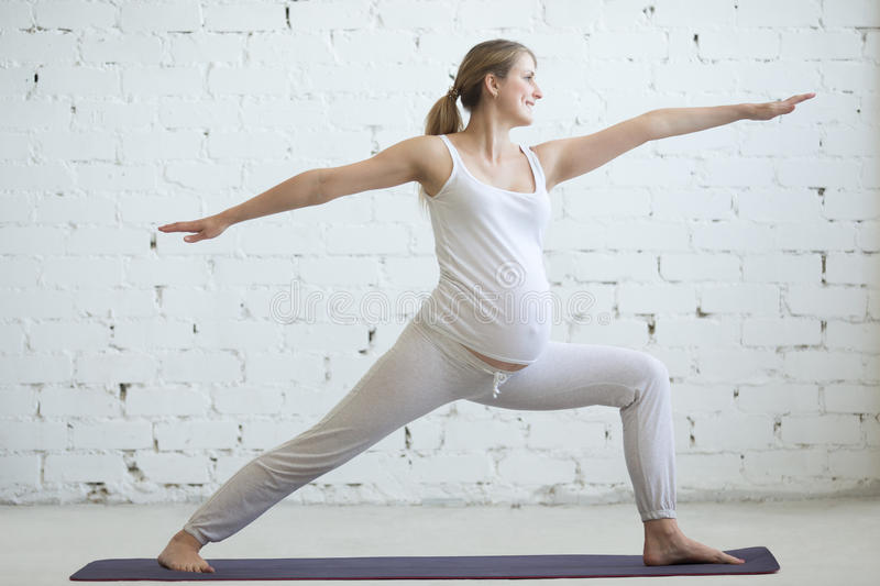 Pregnant young woman doing prenatal yoga. Warrior Two pose. Pregnancy Yoga and Fitness concept. Portrait of beautiful young pregnant yoga model working out stock photo
