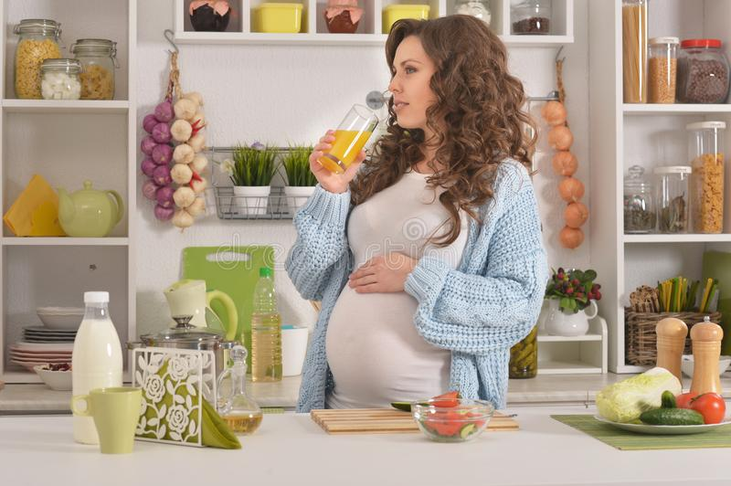 Pregnant young woman having breakfast. Beautiful pregnant young woman having breakfast at kitchen royalty free stock photography
